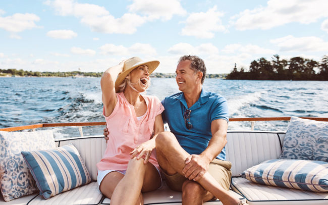 Couple laughing on boat with wake behind
