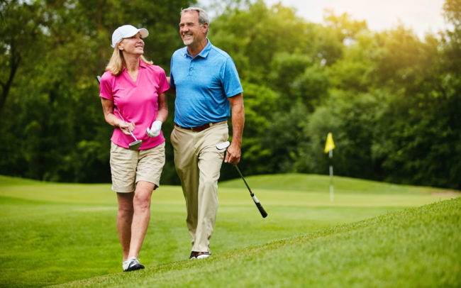 Couple walking together on golf course